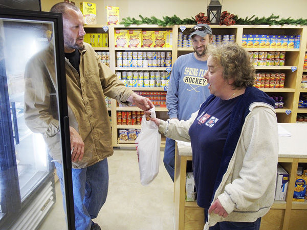 Chatham fisherman Doug Feeney hands frozen dogfish fillets to Falmouth Service Center visitor Tammy Corey of Woods Hole as fellow fisherman Luther Bates looks on. The two fisherman are attempting to popularize the fish as an alternative to cod which is in danger of being overfished.